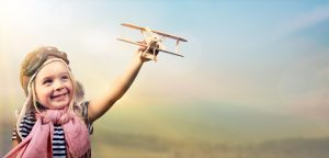 Freedom To Dream - Joyful Child Playing With Airplane Against The Sky